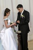 Groom Placing Ring On Brides Hand