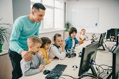 Happy Young Teacher Helping His Teen Students With Diy Robot On Stem Education Class poster
