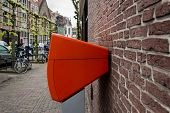 Orange Netherlands Mailbox Post, Mounted On A Brick Wall poster