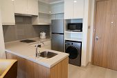 Home Appliances In Small Modern Kitchen. Corner Counter With Electric Stove, Sink And Cooker. Freeze poster