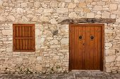 Ancient Door And Windows On A Stone Wall In An Ancient Monastery poster