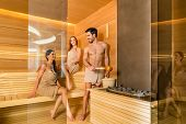 Full length of three young and beautiful people smiling while socializing in a wooden dry sauna heat poster