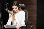 Hispanic Young Female Radio Host Sitting At A Table With Headphones Reading A Script And Broadcastin poster