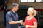 stock photo of auto repair shop  - Young woman collecting care from repair shop - JPG