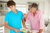 stock photo of sulky  - Father making teenage son do housework - JPG