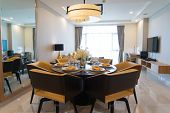 Modern dining room with flower arrangement and mirror. Futuristic chandelier above setting table with comfortable chairs around. Modern design of studio apartment concept