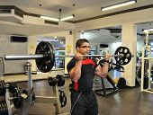foto of upper thigh  - Professional Fitness Instructor Performing Biceps Barbell Curl exercise - JPG
