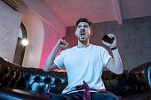 Young Man Watching Football Game On Television, Celebrating Goal, Crazy Happy Jumping On Couch At Ho poster