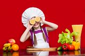 Happy Little Girl In Chef Uniform Cuts Fruit In Kitchen. Kid Chef. Cooking Process Concept poster