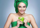 Good Morning! Attractive Girl In Green Towels With Cup Of Tea On Blue Background. poster