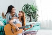 Asian Young Lesbian Couple Playing Guitar For Her Lover With Love Moment In The Bedroom Surrounded W poster