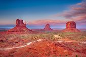Beautiful dramatic sunset over the East, West Mitten Butte and Merrick Butte in Monument Valley. Uta poster