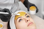 Close Up Of Beautician Applying Gold Mask On Face Of Gorgeous Woman In Beauty Salon. Beautiful Clien poster