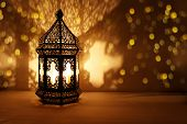 Ornamental Arabic Lantern With Burning Candle Glowing At Night And Glittering Golden Bokeh Lights. F poster