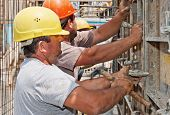 Construction Workers Positioning Cement Formwork Frames poster