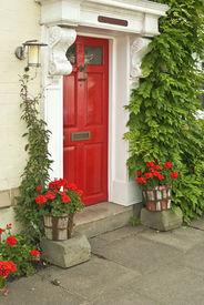 picture of front door  - house with red front door in street with flowers - JPG