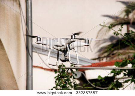 poster of Modern White Quad Copter Drone With 4k Digital Camera Is Flying In The Air, To Take Photos And Recor