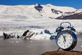 Alarm clock in front of melting glacier and icebergs climate change global warming concept Iceland poster
