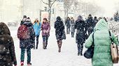 Winter City Sidewalk. Rear View Of People Walking Along An Icy Snowy Pavement. City Dwellers In The  poster