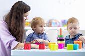 Nursery Kids Play With A Teacher In Kindergarten poster