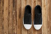 Black Gumshoes With A White Sole Stand On A Wooden Floor. Top View Of Classic Sneakers, Wooden Backg poster