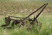 stock photo of horse plowing  - An antique horse drawn plow sits abandoned in a field - JPG