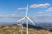 View Of A Mountain Landscape With Wind Mill Turbines On Top Of Mountains, Blue Sky As Background In  poster