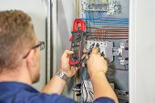 Electrician Man Measures Voltage With Multimeter In Electrical Cabinet. An Electrician Is Checking T poster