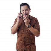 Portrait Of  Young Asian Man Wearing Batik Shirt Crying To Get Bad News On Phone, Sad  Crying Expres poster