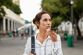 Beautiful mature businesswoman using mobile phone for communication over speaker. Business woman ins poster