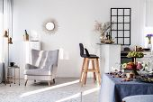 Trendy Grey Armchair Next To Two Black Wooden Bar Stools In Fashionable Kitchen And Dining Room Inte poster