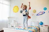 Kids Play Astronaut. Little Boy In Space Costume Jumping On Bed With Rocket. Solar System And Planet poster