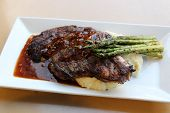 Simple White Dish With Large Piece Of Tender Steak On Top Of Mashed Potatoes, Spears Of Asparagus To poster