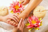 foto of foot massage  - Woman enjoying a feet massage in a spa setting  - JPG