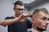 Guy Get A Haircut In A Barbershop, A Young Kazakh Barber Cuts Manually With Scissors And A Comb, The poster