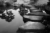stock photo of stepping stones  - Stepping stones bridge across a pond in a Japanese Garden - JPG