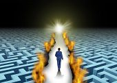 stock photo of trailblazer  - Innovative leadership and trail blazing or trailblazing business concept with a businessman walking through a maze or labyrinth that is open due to a burning path as a symbol of creative solutions - JPG