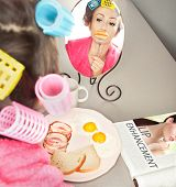 picture of lip augmentation  - Woman with sausages on a fork simulating lip enhancement while having breakfast - JPG