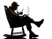 stock photo of sherlock  - sherlock holmes with computer laptop silhouette sitting in rocking chair in studio on white background - JPG