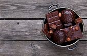 stock photo of melchior  - Bowl with chocolate nuts on a gray wooden background - JPG