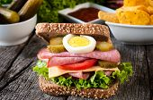 stock photo of raw chicken sausage  - Big toast sandwich with sausage on the wooden table - JPG