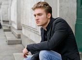 stock photo of posh  - Attractive blond young man in jeans and jacket sitting outdoors looking off camera - JPG