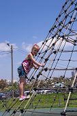 Girl Climbing On Rope Ladder Against Sky