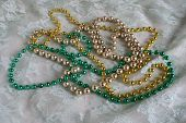 stock photo of debauchery  - three sets of mardi gras beads are displayed on a background of lace - JPG