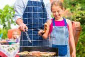 picture of tong  - Father and daughter making barbecue in the garden in summer with sausages and meat - JPG