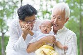 pic of crying boy  - Asian crying baby comforted by grandparents at outdoor garden - JPG