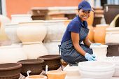 happy african female hardware store worker selling flower pot