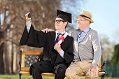 Male graduate and his father taking selfie outdoors
