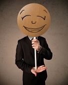 Businessman holding a cardboard smiley face emoticon in front of his head
