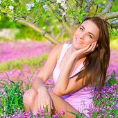 Closeup portrait of nice dreamy girl sitting down on pink flowers field in apple tree garden, watchi